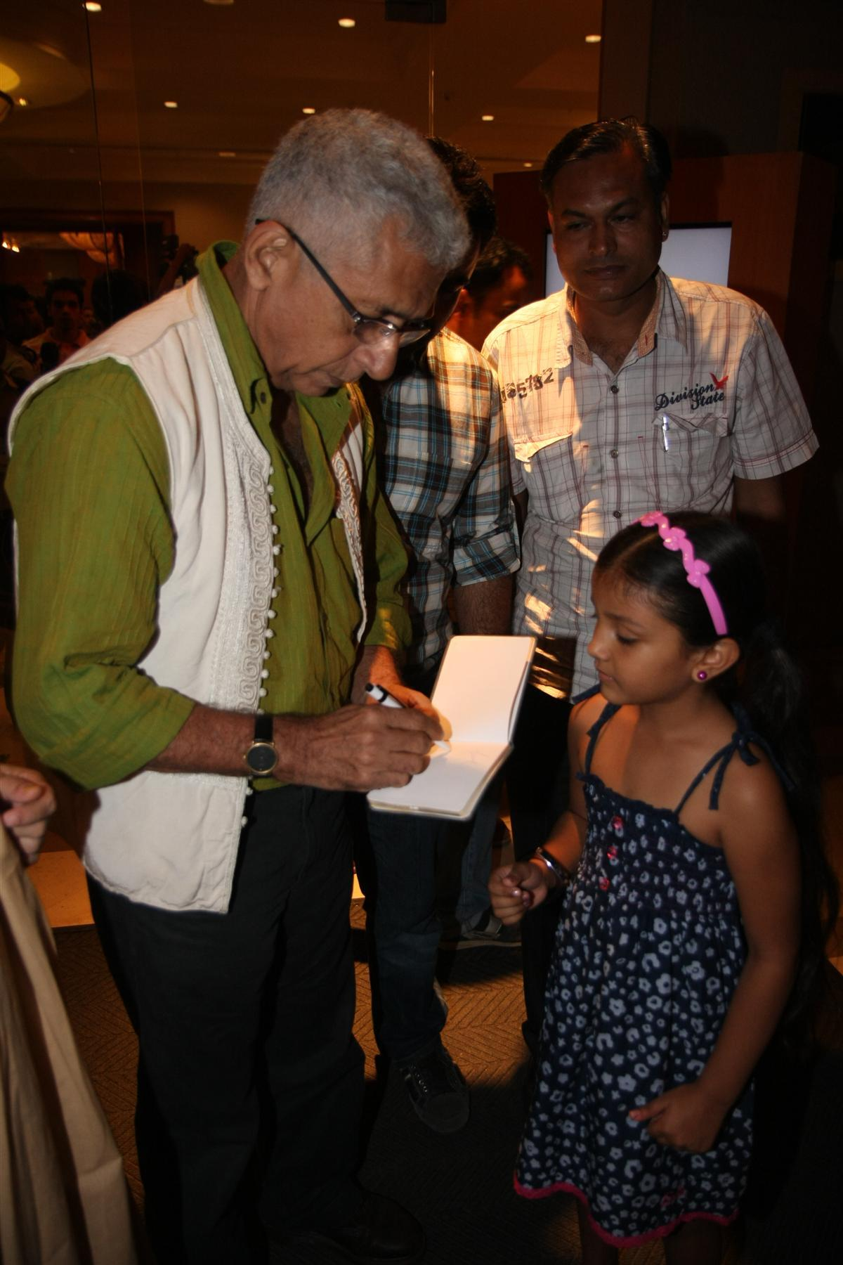 Naseeruddin Shah signing an autograph for a little girl